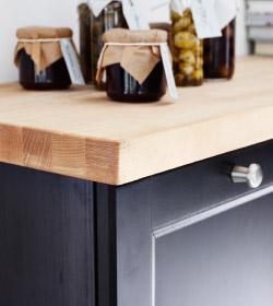 Крупным планом: деревянная кухонная столешница с банками маринадов и варений